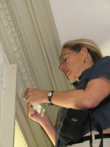 Dr. Buck collects a sample of wallpaper from the top of a window frame in the drawing room.